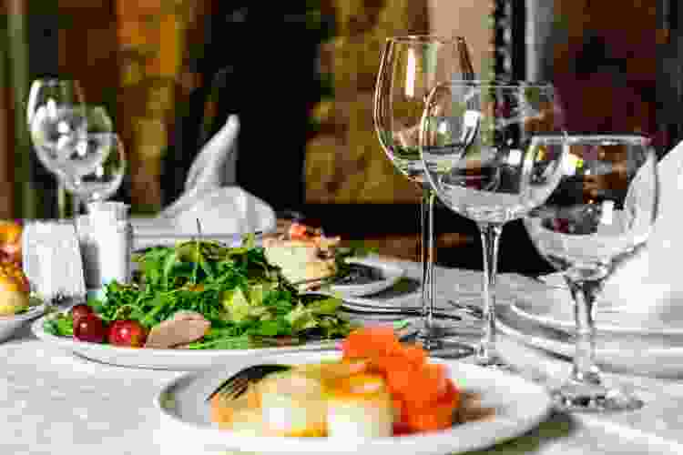 restaurant table with gourmet plates of food and wine glasses