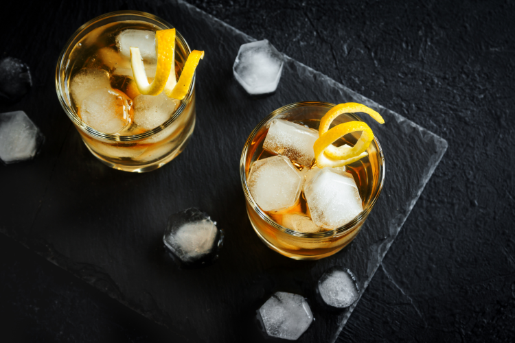 two whiskey cocktails with citrus peel