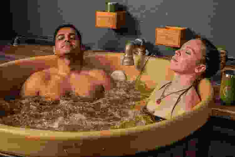 couple soaking in a round tub at the beer spa