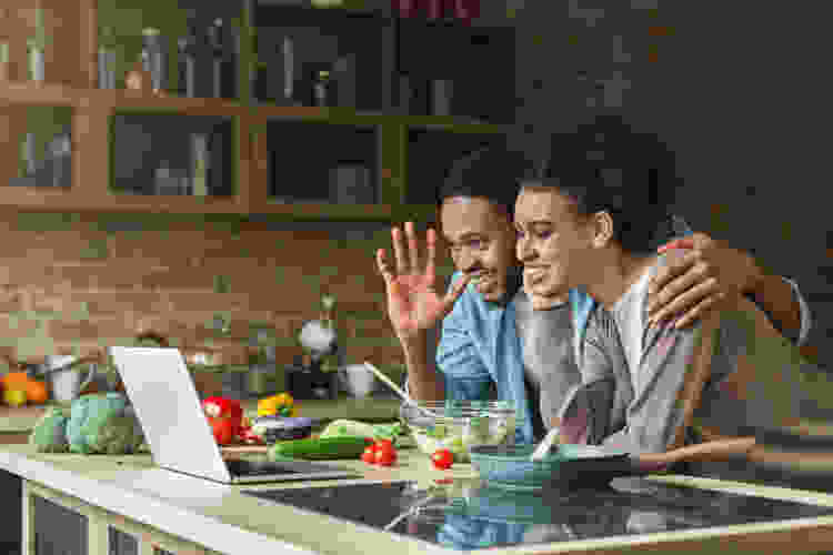 young couple waving at laptop during an online cooking class