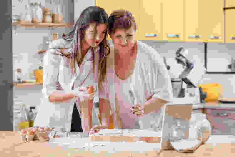 mother and daughter taking an online cooking class at a virtual holiday party