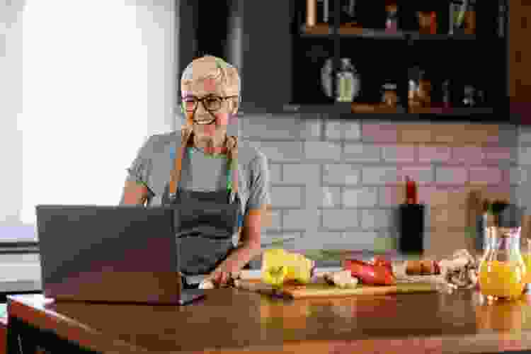 woman taking an online cooking class in her kitchen