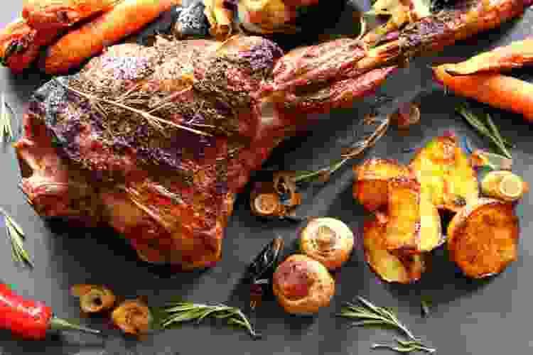 roasted leg of lamb with potatoes, mushrooms, carrots and rosemary