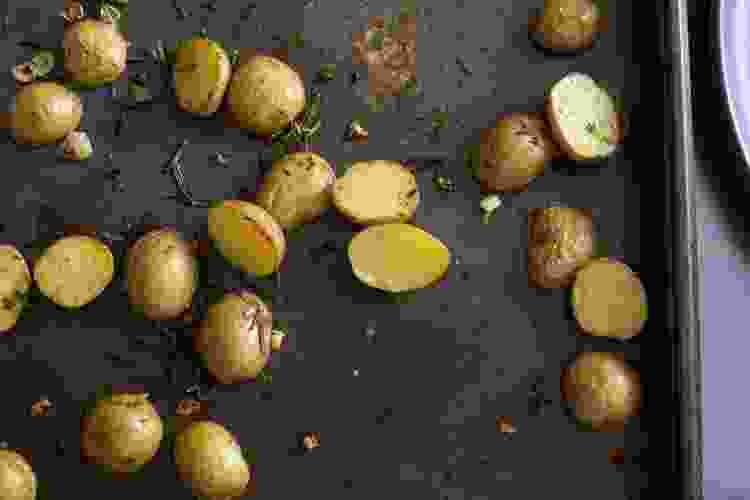 New potatoes on a baking sheet with rosemary