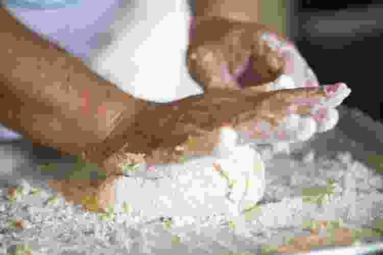 chef kneading deep dish pizza dough on a floured work surface
