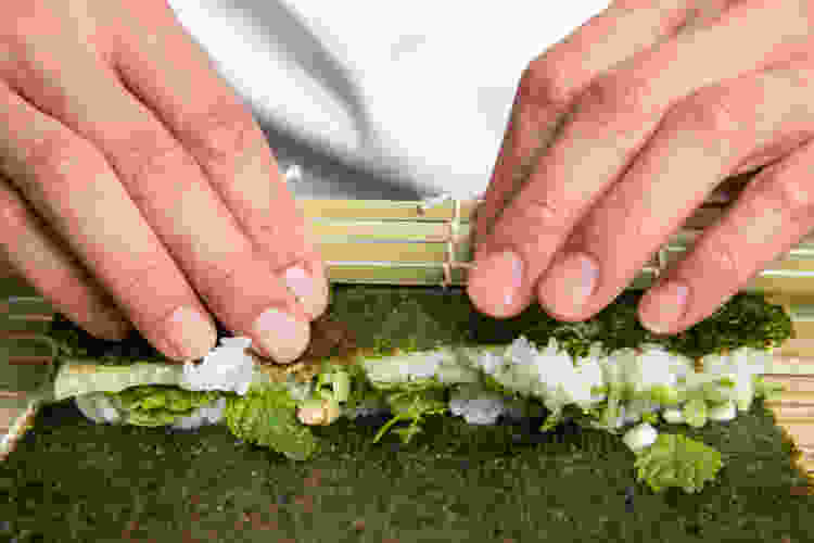 chef rolling sushi with a bamboo mat