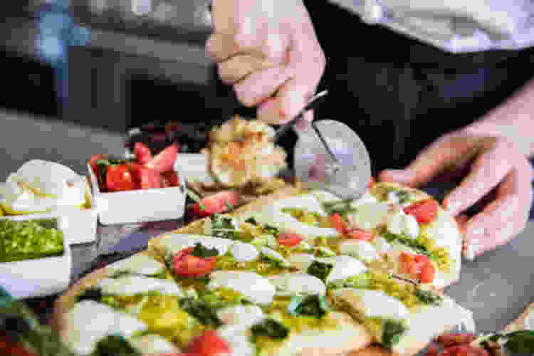 chef rolling a pizza cutter through a flatbread during a cooking class