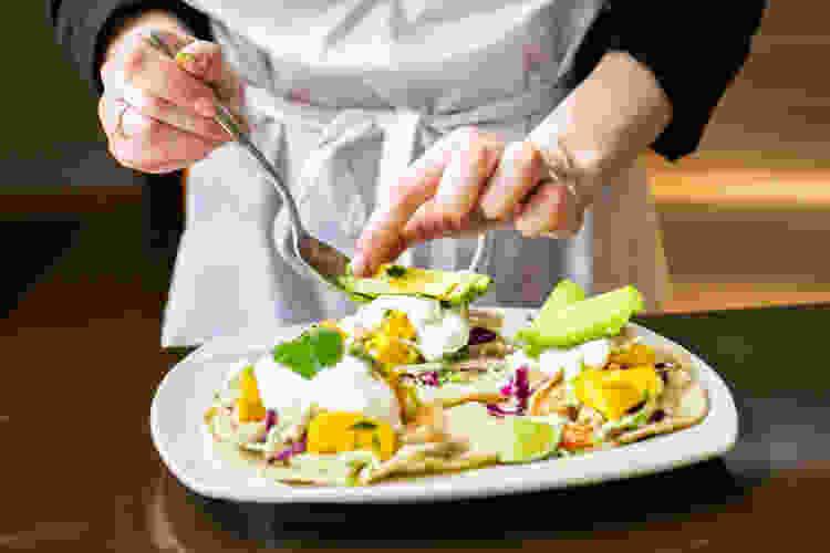 private chef plating avocado onto tostadas