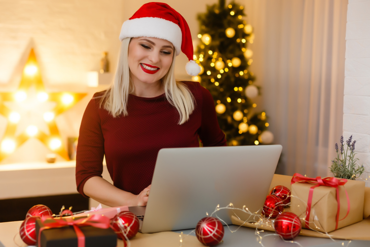 woman in a santa hat planning a holiday party on her laptop