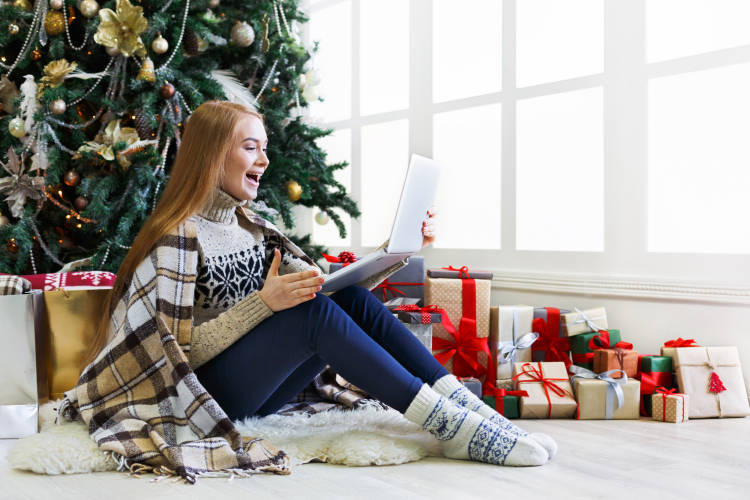 young woman playing virtual never have i ever by a christmas tree