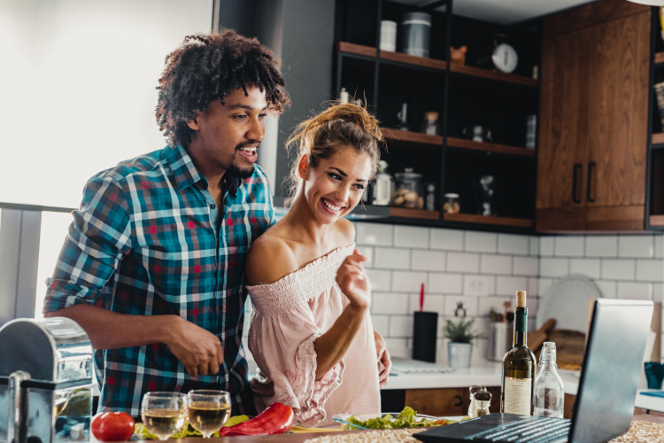 young couple taking an online cooking class