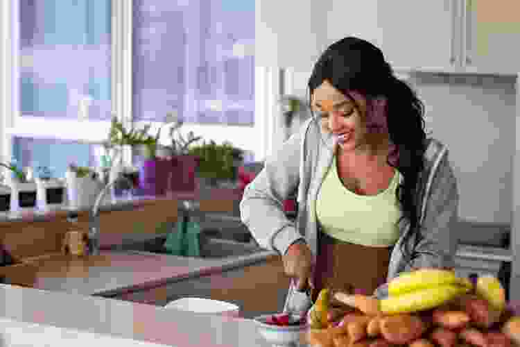 young woman slicing fruit in a kitchen