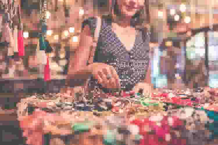 woman looking through jewelry at a store