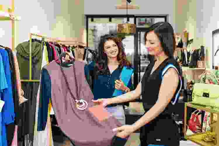 woman picking out a dress in a clothing boutique