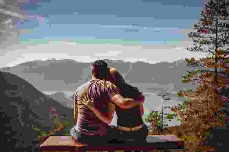 young couple sitting on a bench looking out at the scenery