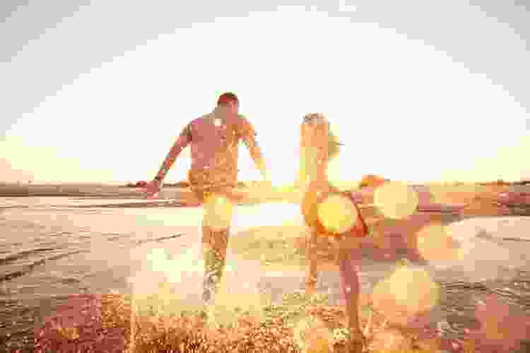 couple running along the beach at sunset