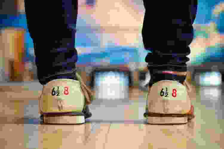 close up of bowling shoes before rolling a bowling ball