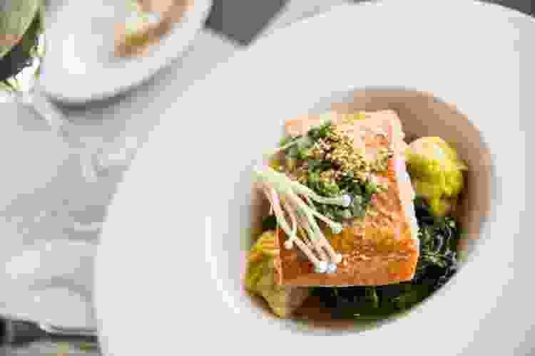 plated salmon with braised greens, enoki mushrooms and white wine