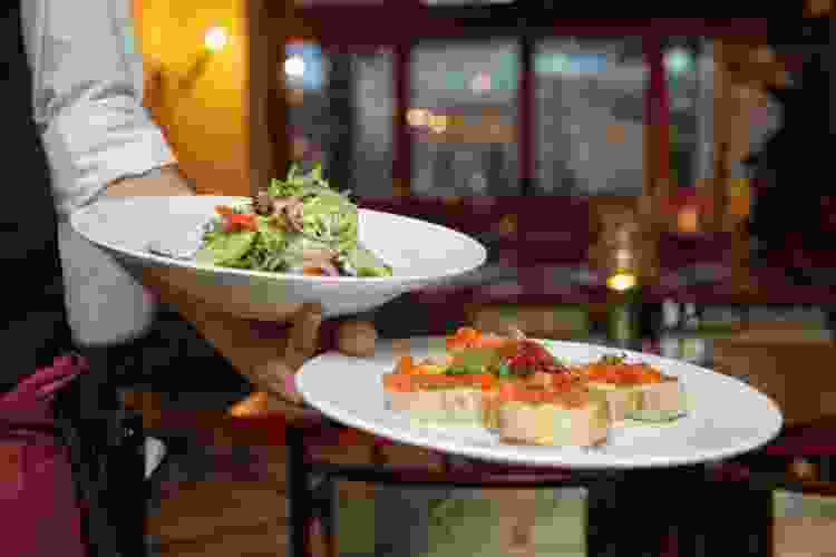waitress carrying plates of food in a gourmet restaurant