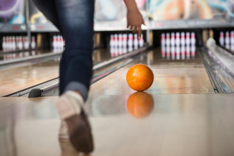 person rolling an orange bowling ball down a bowling lane