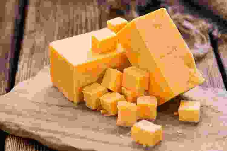 cheddar cheese on a wooden cutting board