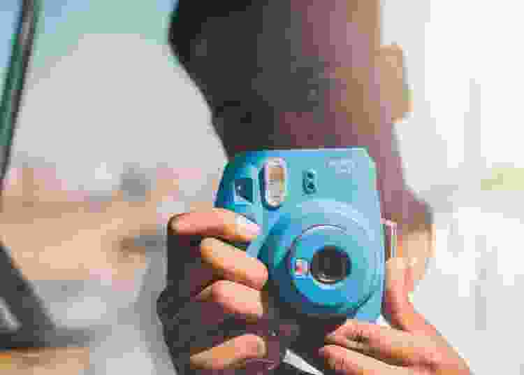 young man taking photos with an instax instant camera