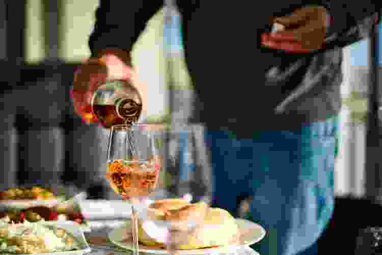 man pouring rosé wine with dinner