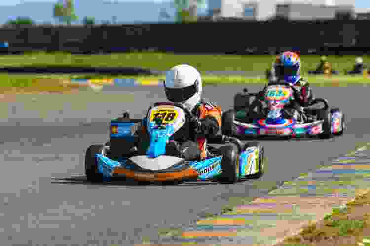 drivers racing go-karts around a racetrack