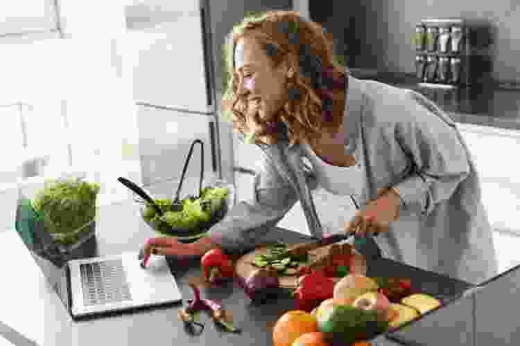woman chopping vegetables during an online team building activity