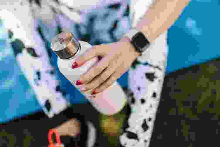 woman holding a metal water tumbler