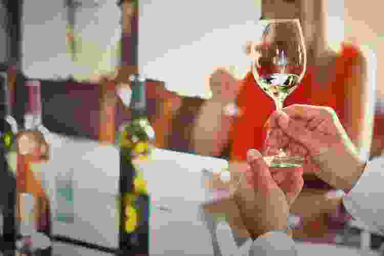 wine taster holding up a glass of wine to evaluate it