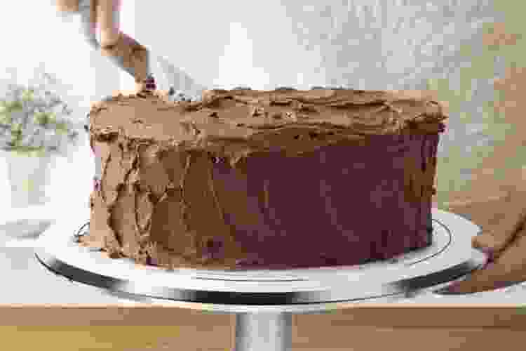 chef icing chocolate cake on a rotating cake stand
