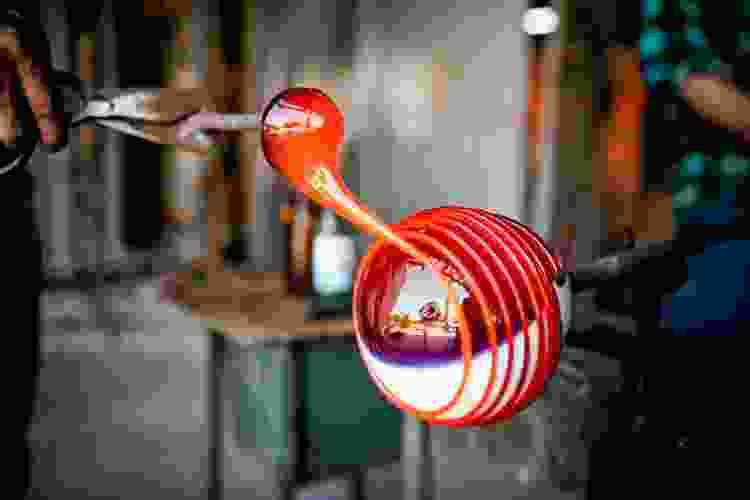 artist spinning hot glass on a rod