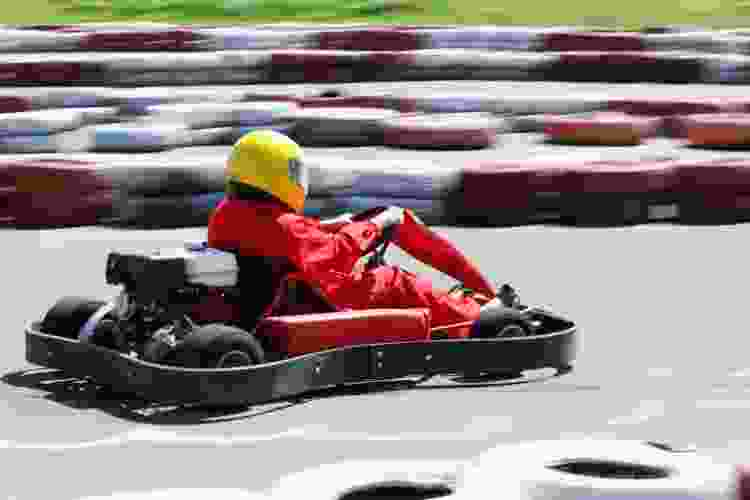 driver racing a go-kart on a track