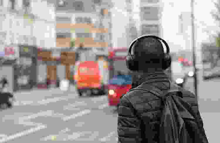 Young man walking down city streets wearing wireless headphones
