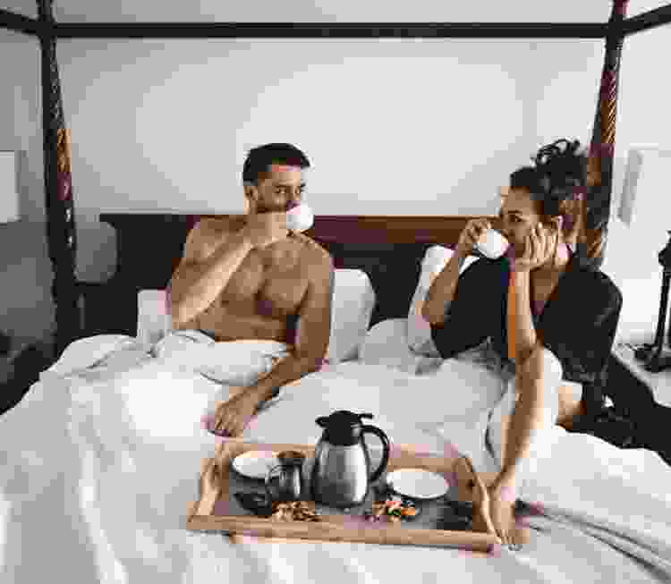 young couple drinking coffee in their hotel room
