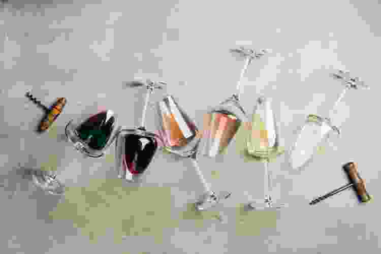 glasses filled with different wines with a corckscrew