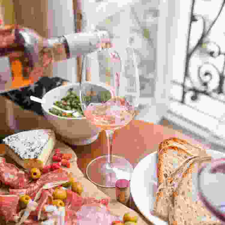 pouring a glass of rose wine at a private home wine and cheese tasting