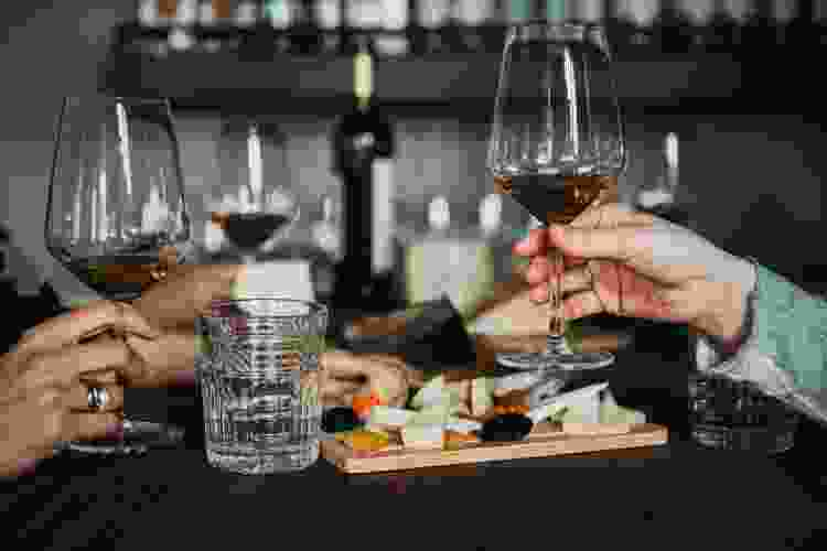 friends holding long-stem wine glasses while enjoying a cheese board