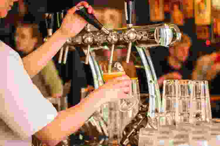 bartender pouring draft beer from a tap