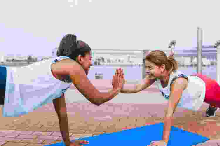 women high-fiving while exercising together