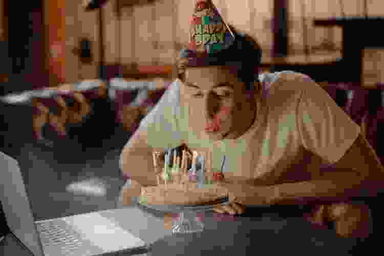 young man blowing out candles during a virtual birthday party