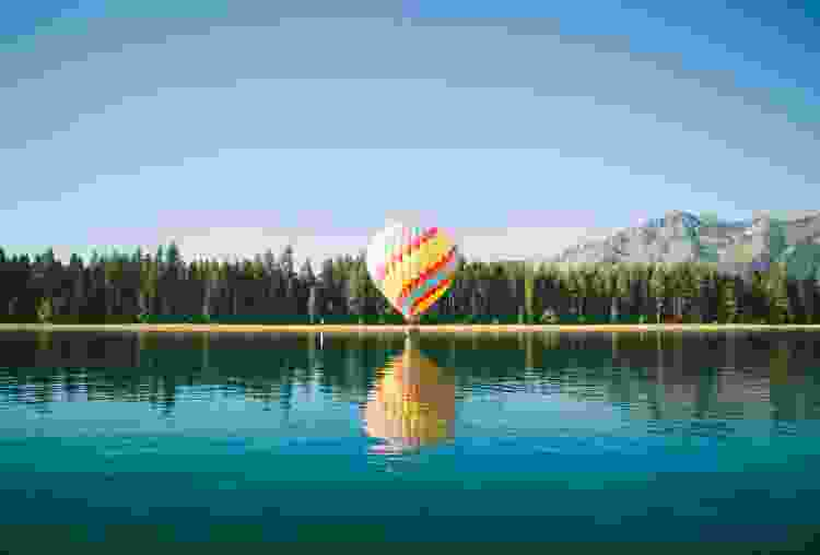 hot air balloon preparing to take flight over a lake