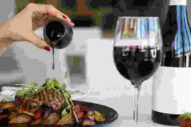 pouring demi glass over filet with an accompanying glass of pinot noir