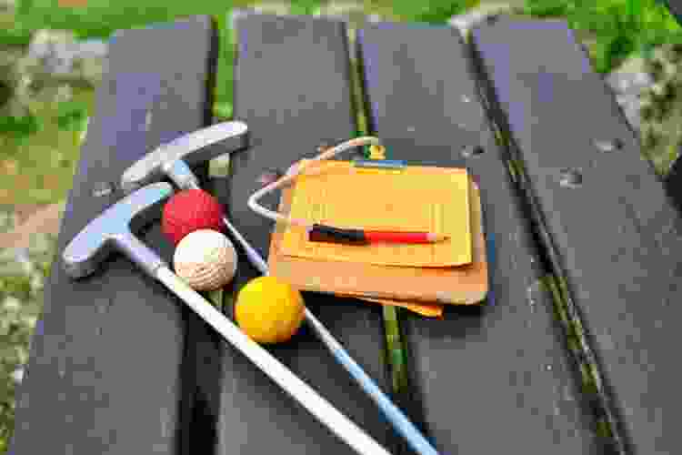 mini golf clubs, balls and score card on a table