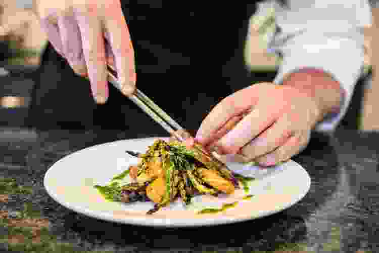 new york city chef plating food in a restaurant