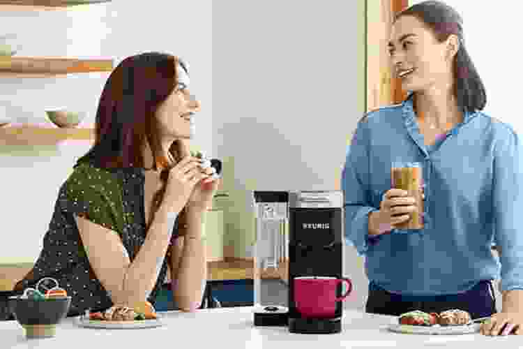 woman chatting in front of a keurig coffee machine on the counter