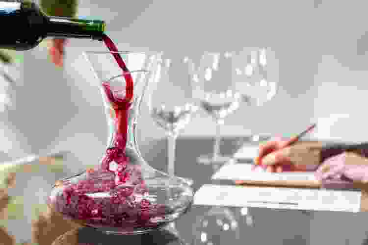 wine being poured into a decanter for a wine tasting