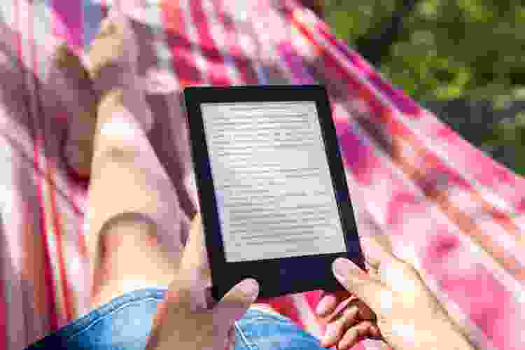 woman reading a kindle paperwhite on a hammock