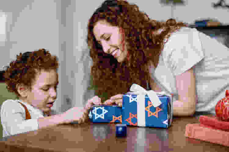 mother and young daughter wrapping Chanukah presents